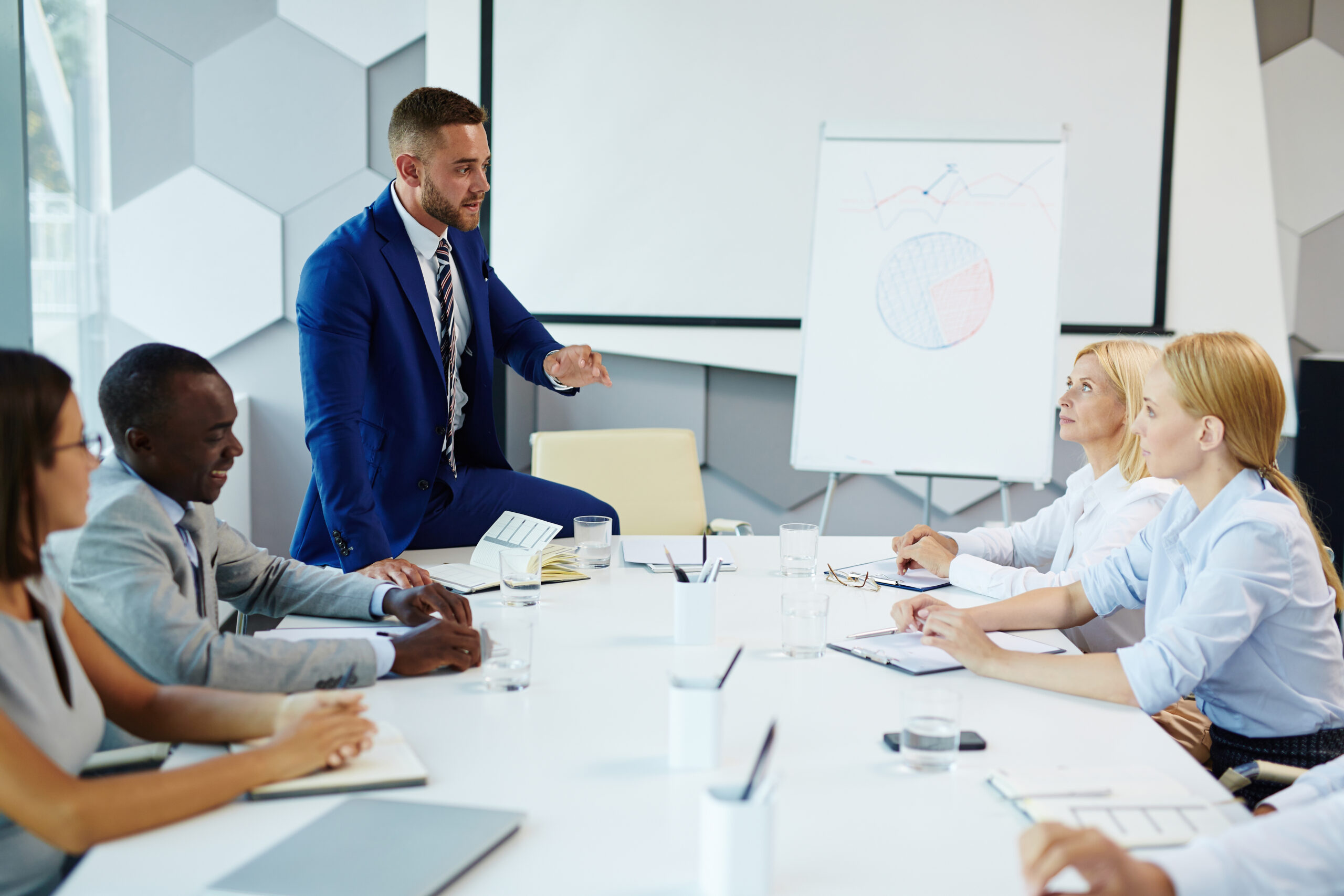 Elegant businessman explaining viewpoint to co-workers at meeting